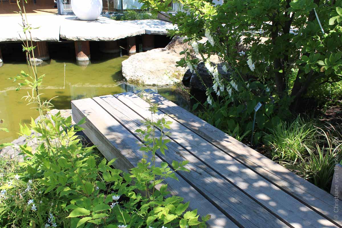 Ein Holz-Steg schwebt im Gehölzschatten über dem Naturteich