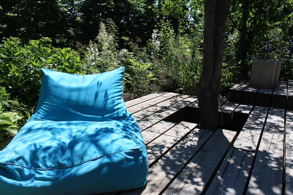 Ein Sitzplatz am Teich unter dem lichten Schatten eines Gehölzes
