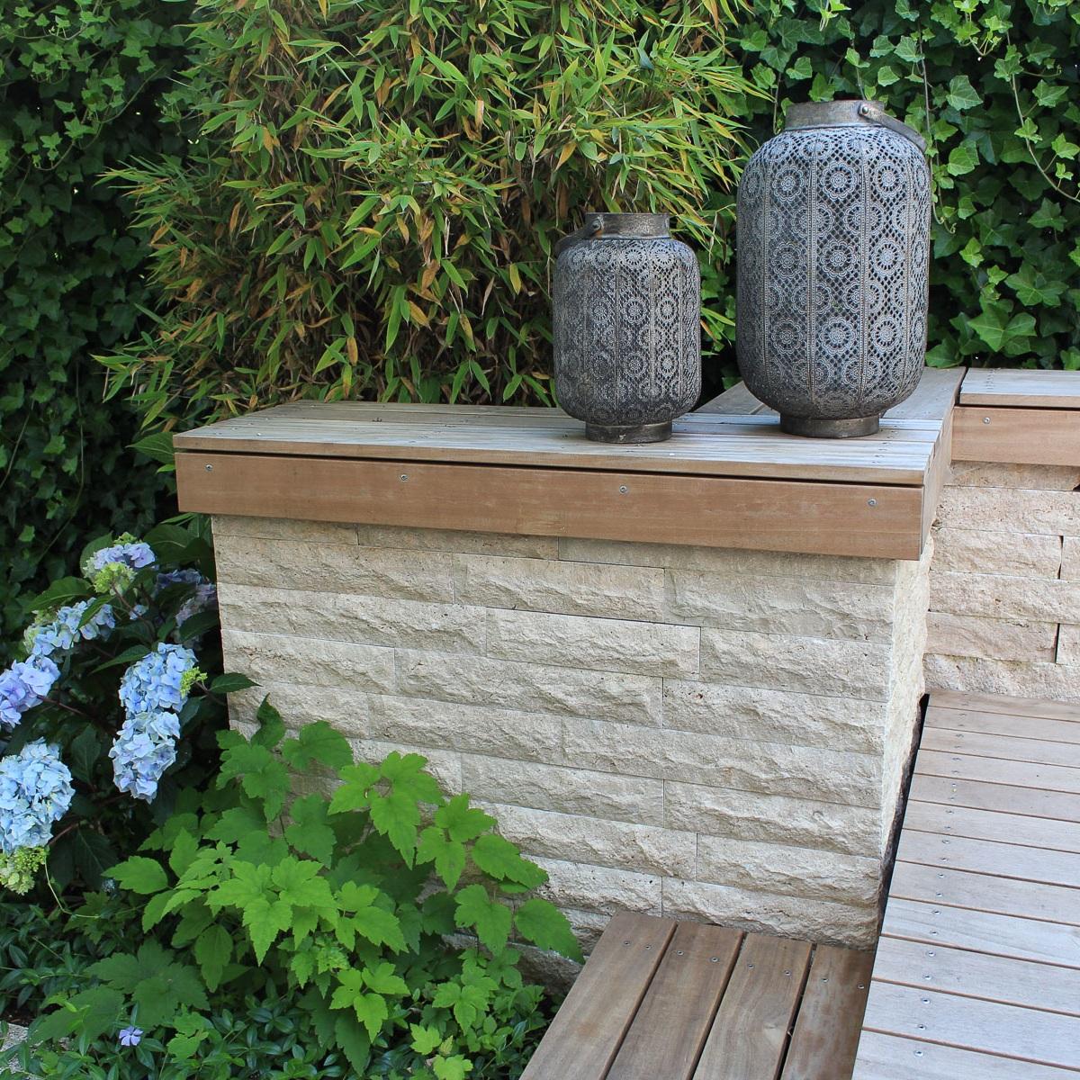 Symbiose aus Holz und Stein: Gartenmauer und Holzdeck mit Stufen