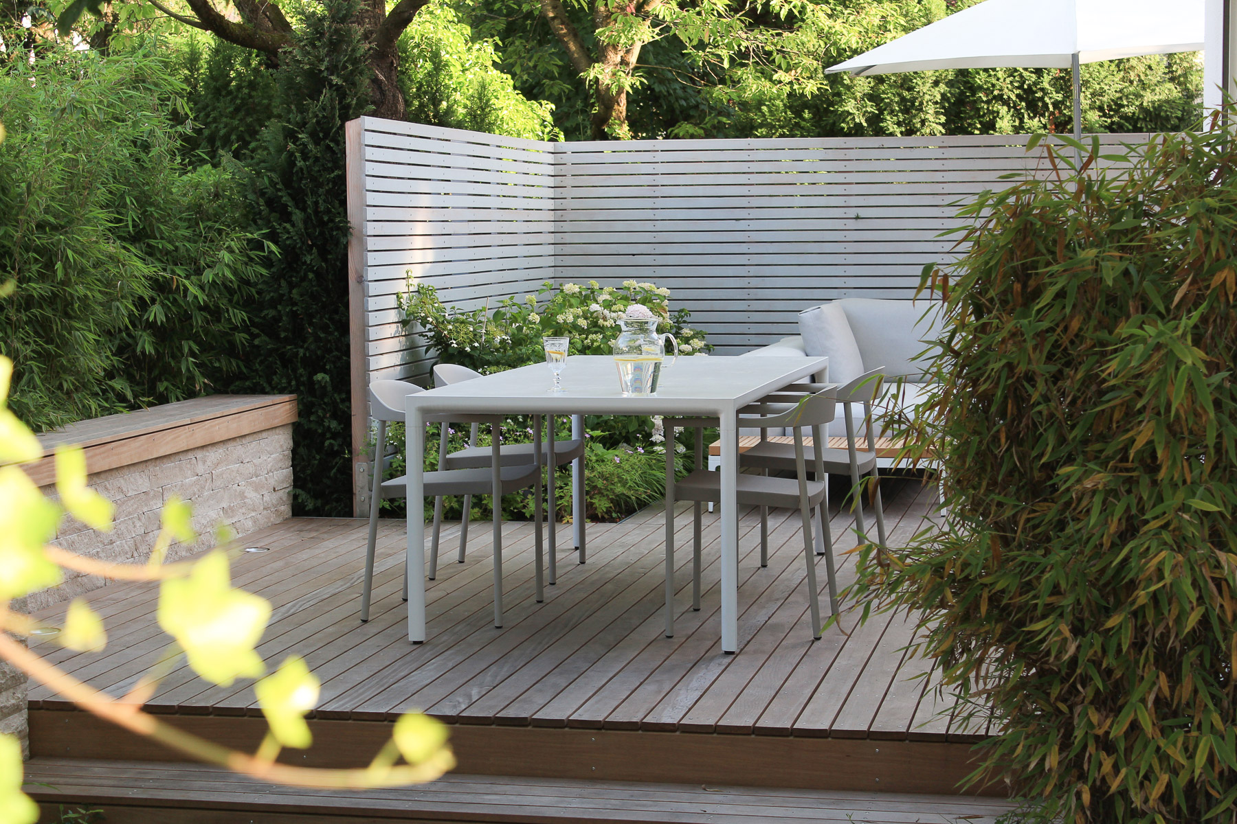 Blick in die Gartenoase mit heller Sichtschutzwand