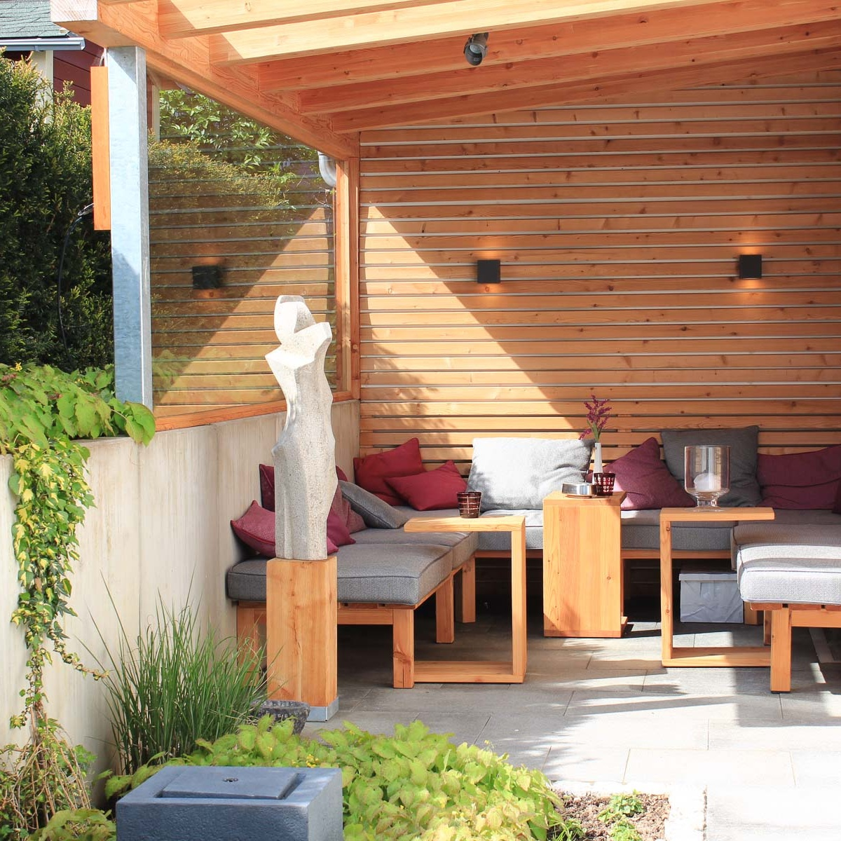 Eine Steinskulptur gliedert den Garten, bringt Höhenstruktur und dient als Blickpunkt auch vom Zugang.