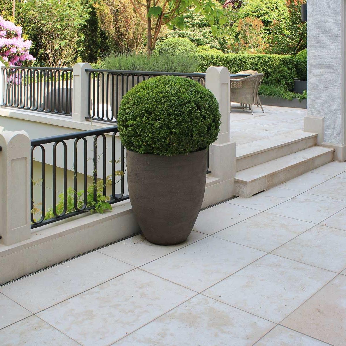 Zwei Terrassen, die durch eine Treppe gegliedert werden, werden mit großen Pflanzgefäßen eingerichtet.