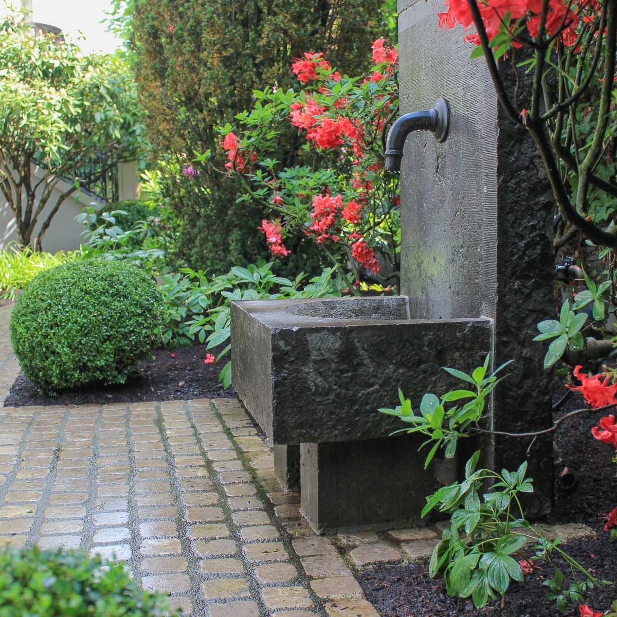 Ein Brunnen aus Belgischem Blaustein wird von Azaleen und Rhododendren gerahmt.