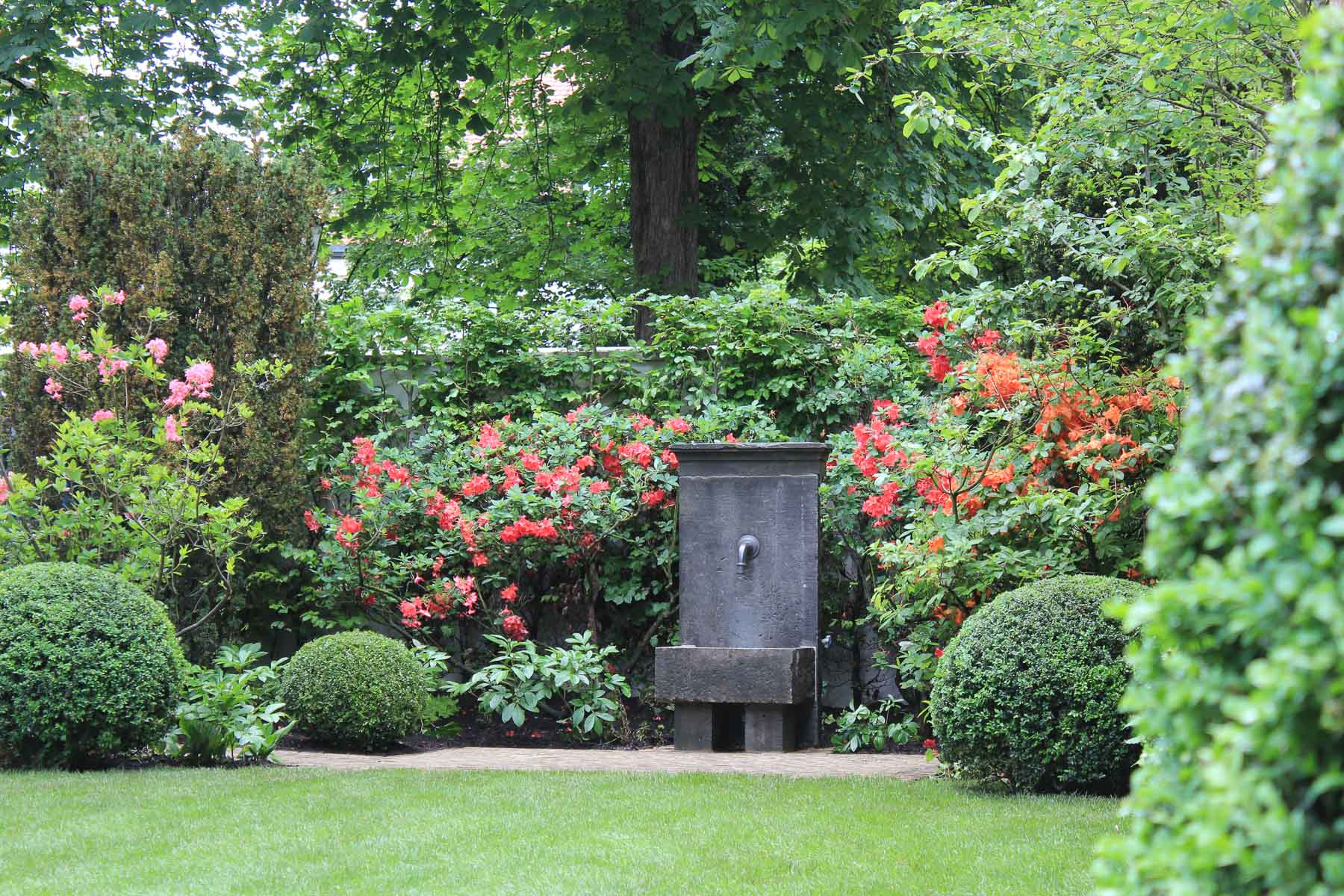 Der Brunnen aus Belgischem Blaustein ist ein Blickpunkt am Ende der Rasenfläche.