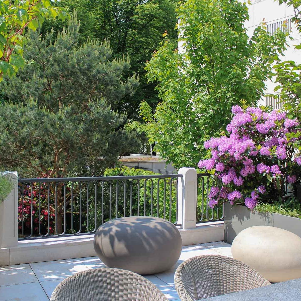 Sitzkiesel aus Ton sind zugleich auch Blickpunkte auf der Terrasse, die von einem Hochbeet eingefasst wird.
