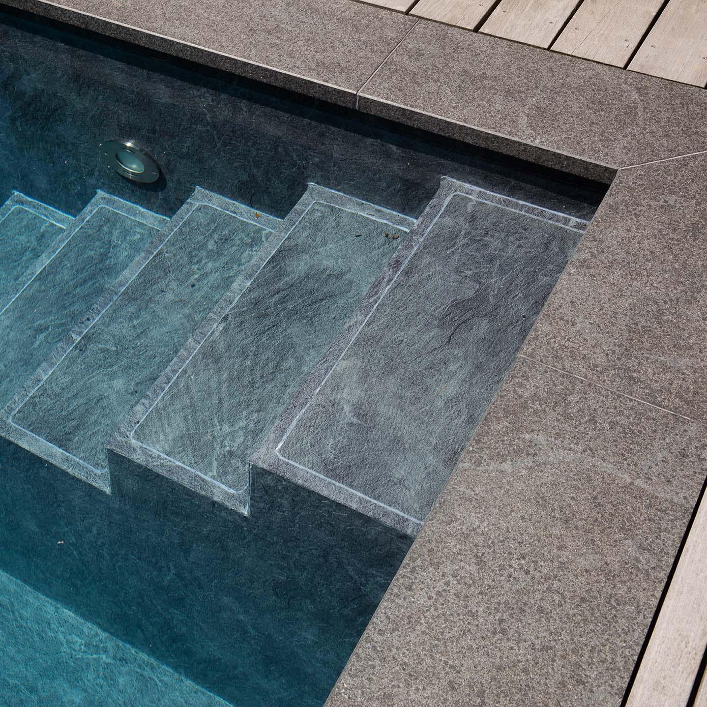 Materialkombination am Pool mit Itauba-Holz und Granit in dunklem Farbton.