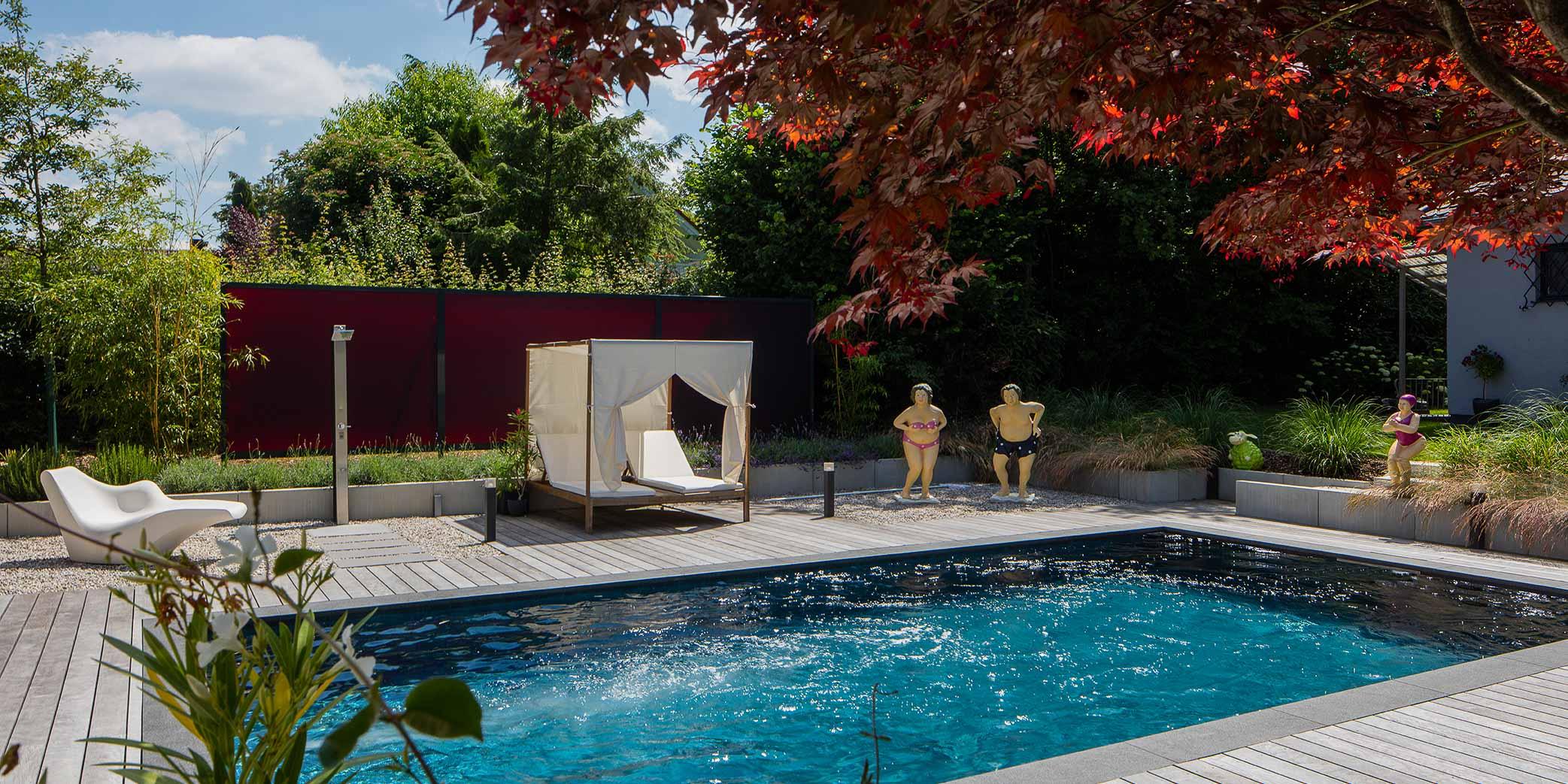 Die Sichtschutzwand greift das dunkle Rot des Fächerahorns auf, auch hinter dem Swimmingpool.