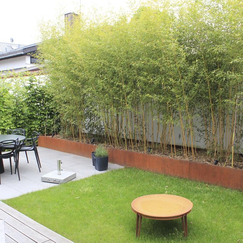 Ein Hochbeet aus CorTen-Stahl ist mit Bambus bepflanzt.