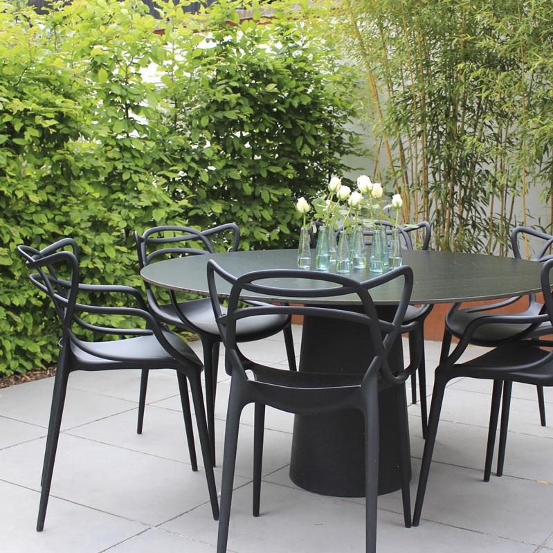 Die schwarzen Gartenmöbel heben sich vor dem Grün der Pflanzen und dem Stahl-Beet deutlich ab.