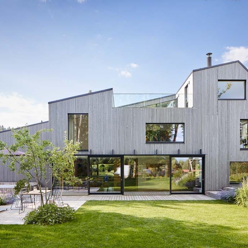 Bavarian Modernism: die Fassade aus vorvergrautem Lärchenholz findet ihre Fortsetzung im Holzdeck.