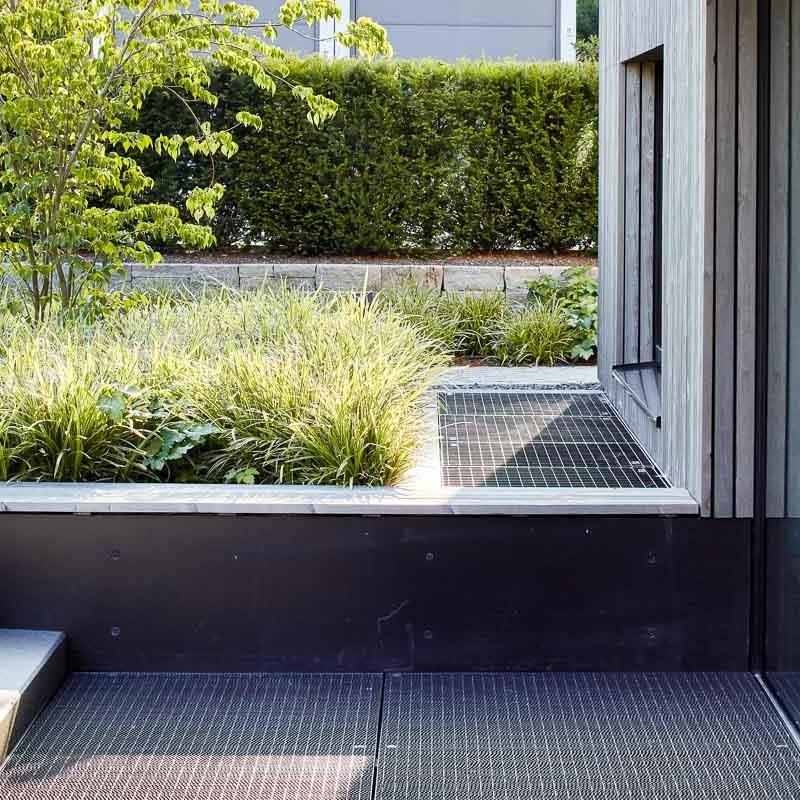 Die Sitzbank vor der Haustür führt die Fassadenlattung fort.