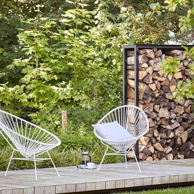 Der Sitzplatz auf dem schwebenden Holzdeck ist malerisch vor dem Brennholzlager angelegt.