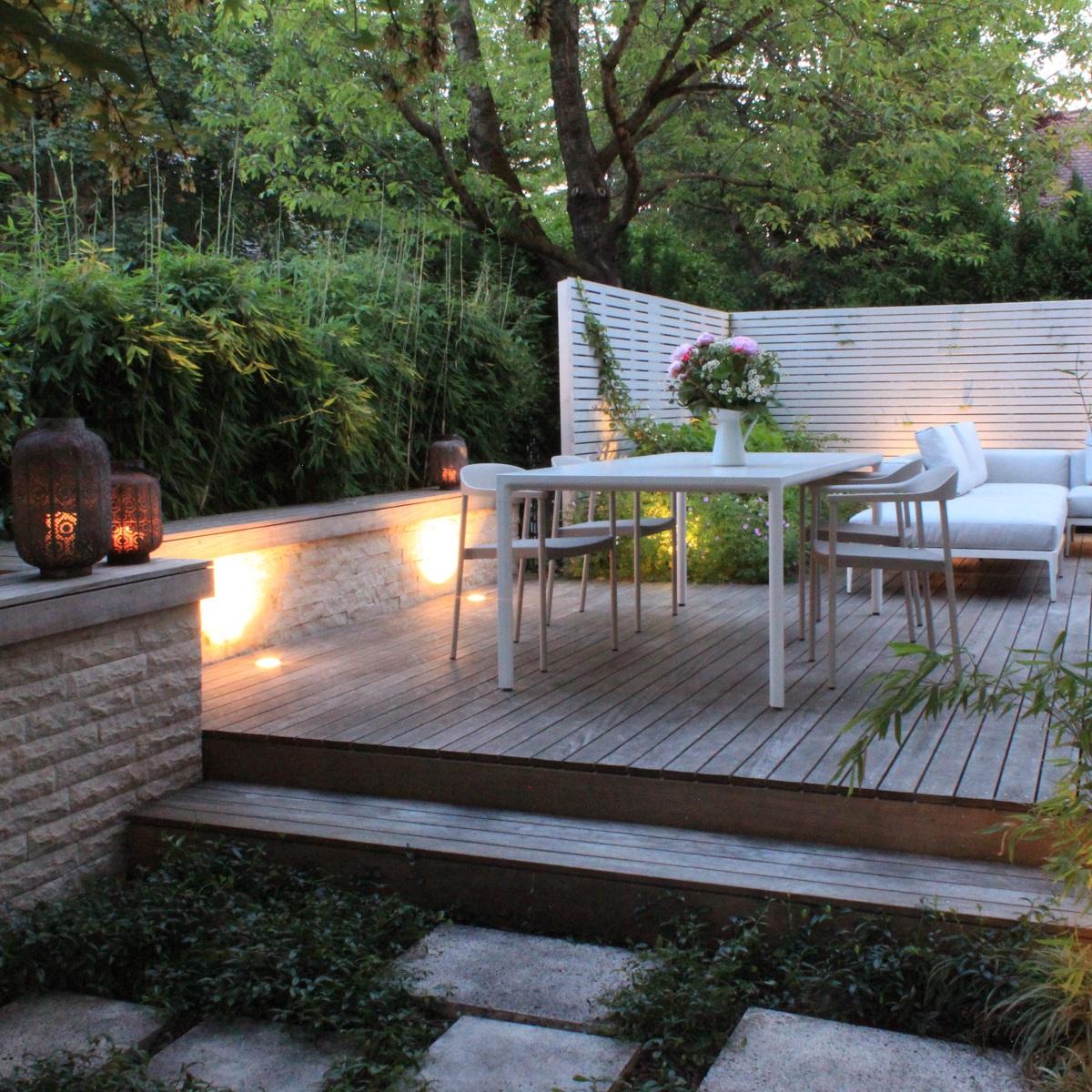 Auf der Natursteinmauer aus Travertin ist eine Sitzbank aus Ipé angelegt.